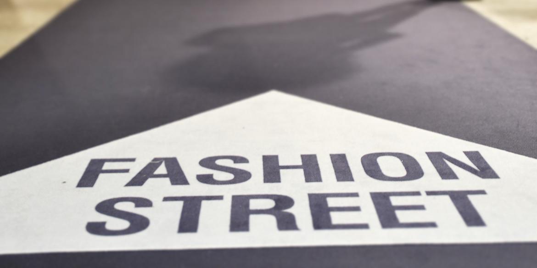 tæppe med teksten fashion street og en pil