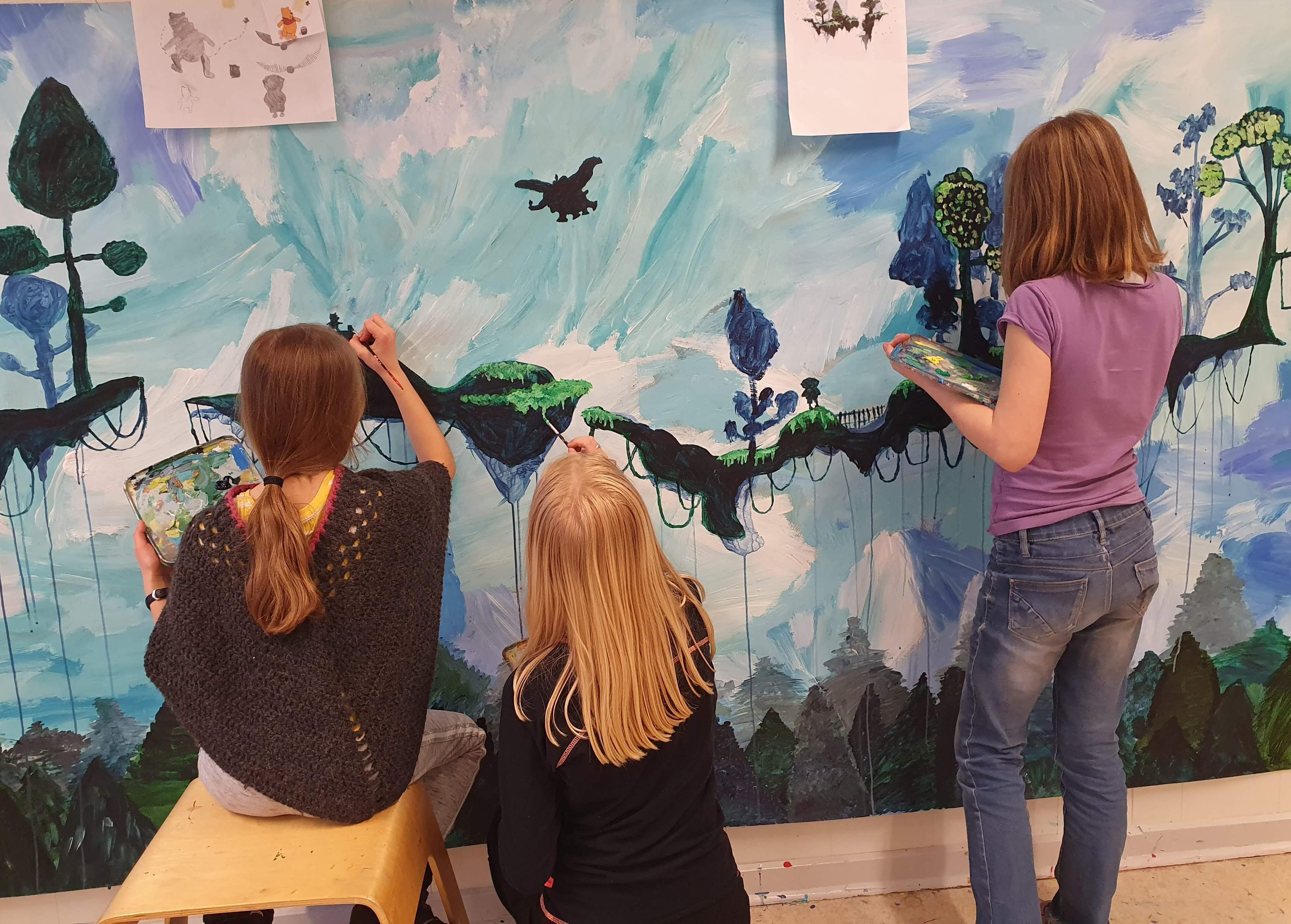 Børn maler et billede sammen.